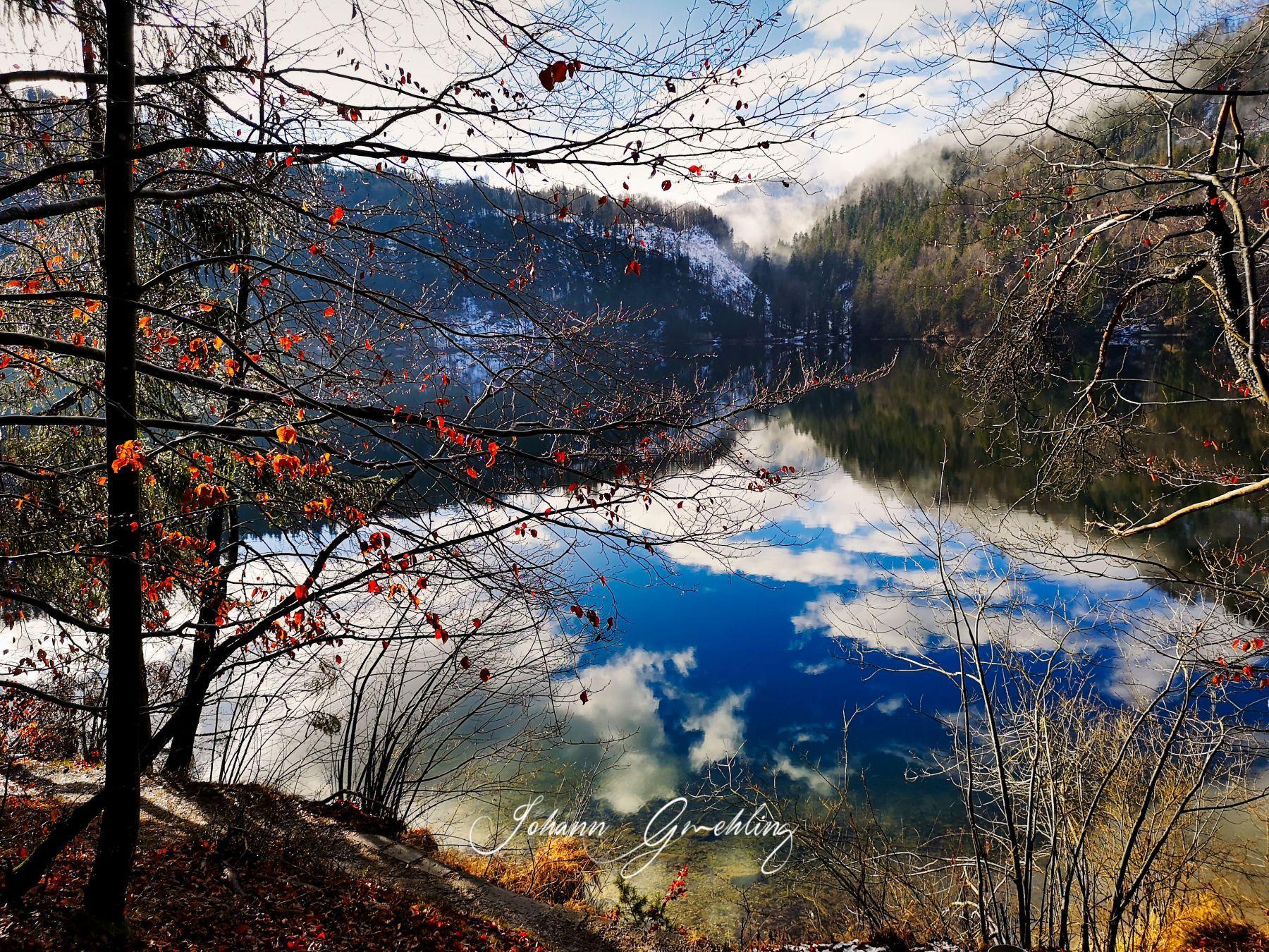 Wasser mit Spiegelung der Woleken und warme Farben am Ufer