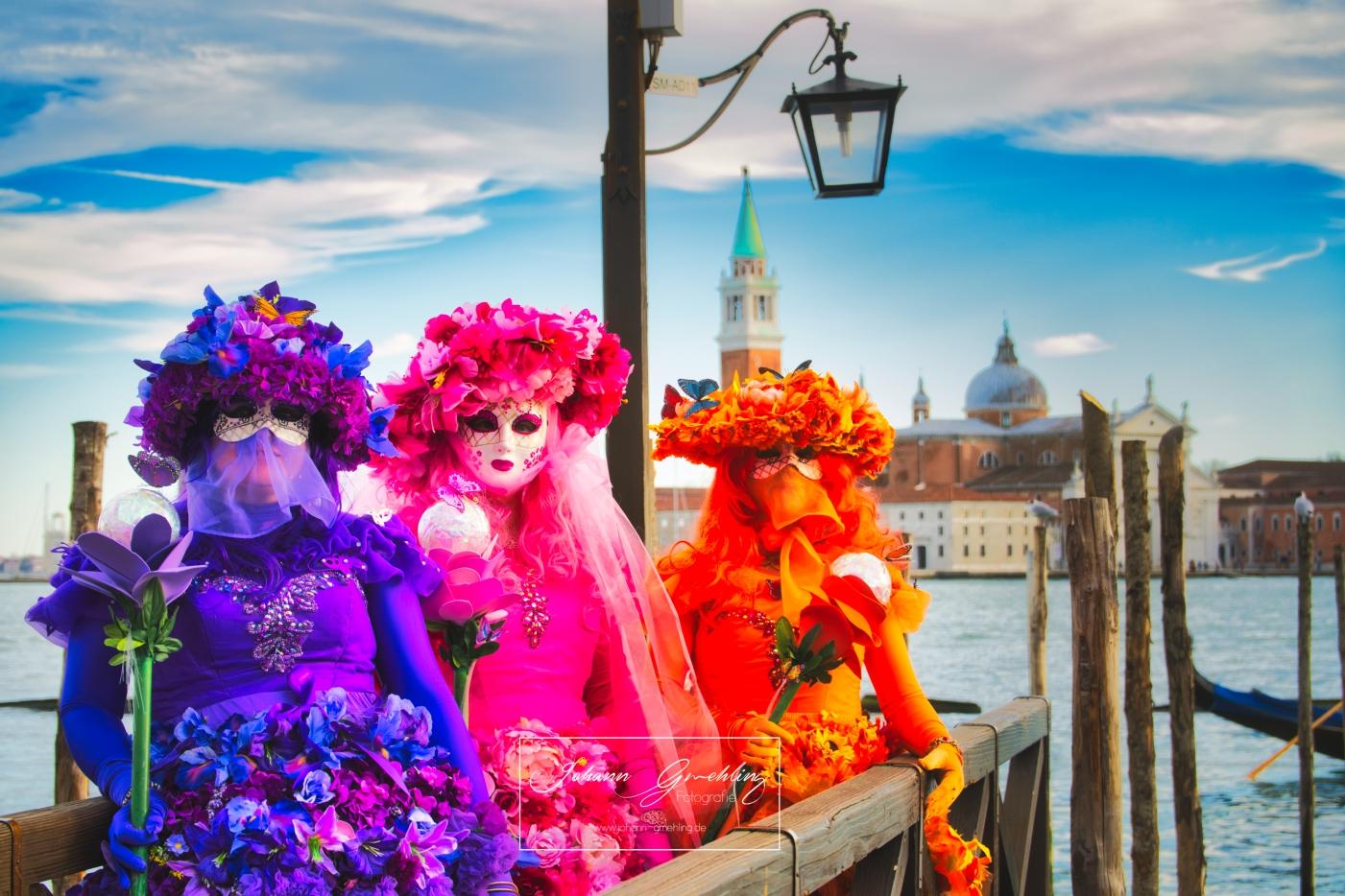 Drei Damen mit bunten Masken am Canale Grande in Venedig